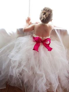 Niña de espaldas con traje blanco y lazo rosa