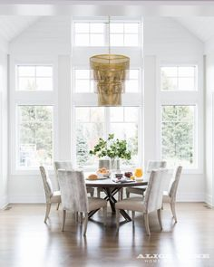 Coastal Contemporary Dining Room. The wall of windows and white shiplap create such a warm vibe paired with this stunning gold chandelier Designed by Alice Lane Photo by Nicole Gerulat