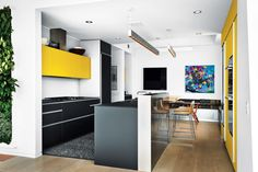 This apartment inNeil Denari'sHL23 building in New York City featurescolorful accents and stunning views of the High Line. Thekitchen features an Artematica Vitrum glass system from Valcucine, artwork by Craig Kucia, and banquette cushion fabrics by Hella Jongerius for Maharam.   Photo by Christopher Wahl.   This originally appeared in How to Design with Yellow.
