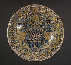 Dish with raised ridge on rim. Earthenware covered on front with presumed tin glaze; on the back with brown translucent glaze. Painted in blue and yellow-brown. In centre a shield of arms for Pope Julius II (Giuliano della Rovere) - an oak tree with acorns; shield supported by two winged dragons and surmounted by papal tiara and crossed keys; field is scattered with rosettes. On rim a continuous pattern of foliage and berries.