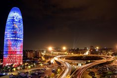 """""""Torre Agbar"""" in Plaza de las Glorias, Barcelona.     The Torre Agbar tower is most impressive at night, when it is illuminated. The tower represents a water fountain that constantly changes its colours. The coloured aluminium sheeting reflects the lights which consist of 40 different colours."""
