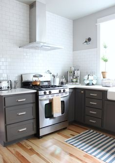 Glassy Tile Wall And Laminate Floor Designed For Kitchen Island Paired With Dark Gray Cabinet Painting