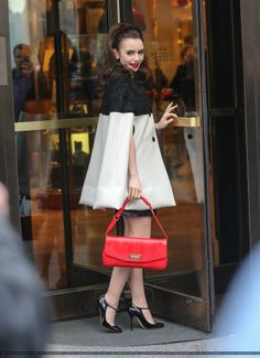 lily collins The actress looked classy in a black and beige Emilio Pucci capelet with a black skirt underneath and black t-strap heels. A red handbag and matching pout completed the photo shoot ready ensem!