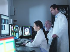 Doctors and scientists looking at screens of Magnetic Resonance Imaging (MRI) 3…