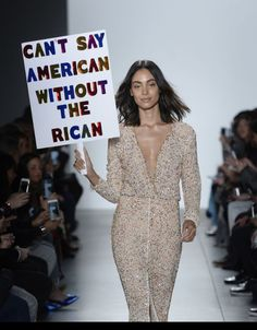 """A model carries a sign that read, """"Can't say American without the Rican"""" during the runway show for Stella Nolasco."""