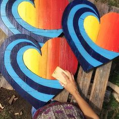 ****Now a 5-6 week wait for delivery on these***   Our Rainbow Wave heart measures 20 x 20 and is made from 100% reclaimed wood. Each wood board is chosen for texture and grain, then hand cut and painted with our own hand mixed colors. The heart is assembled with 20-30 hand cut pieces and secured with both wood glue and nails, with cross braces on the back which makes it very sturdy. We finish the heart with coats of varnish to bring out the wood tones as well as protecting the piece from…