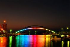 The Xiying Rainbow Bridge is an elevated pedestrian walkway located in Magong, Penghu County in Taiwan. The bridge is lined with a thin neon band that reflects a rainbow onto the water's surface below at night. Taiwan, Street Art, Street Style, Bridge Design, Pedestrian Bridge, Rainbow Bridge, Rainbow Art, Rainbow Colors, To Color