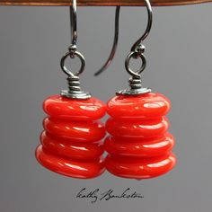 These red earrings feature eight colorful poppy red disk beads that I handmade in my studio. The lampwork beads have been stacked and wire wrapped using sterling silver wire. Bright, colorful, and bea