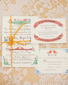 The bride hand-painted the invitation's designs, then scanned and printed them onto card stock. The suites were tied with yarn and mailed in envelopes addressed by the bride and her friends. Each envelope featured a grouping of mismatched postage stamps.