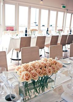 Long glass rectangle vases with peach roses, in a long banquet style table design.