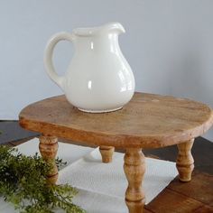 A vintage cutting board and some wooden legs were used to create this wooden pedestal inspired by the Pottery Barn version!