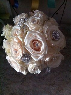Tied bouquet of avalanche roses with diamantes and vintage broaches.