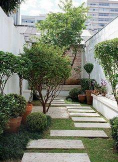 Jardim com bancos de alvenaria, vasos e grama.
