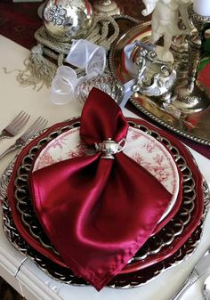 A rich, red colored satin dinner napkin to coordinate with the place setting.