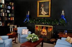 Black walls paired with pale blue upholstery, gold framed painting, bouillotte table lamp - Mario Buatta at the Old Westbury Gardens' 2010 Home for the Holidays Designer Showhouse at Orchard Hill