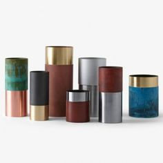 Cylindrical vases created from oxidised metals.