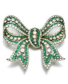 A Belle Époque emerald and diamond brooch, 1910s. Designed as a bow millegrain-set with circular-cut diamonds and calibré-cut emeralds. #BelleEpoque #brooch
