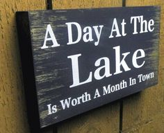 """This rustic wooden pallet sign reads """"""""A Day and the Lake is worth a Month in Town"""""""". It can hang on the wall or stand up on the shelf. What a great addition to your cabin decor!It is made from recla"""
