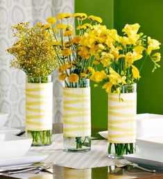 Cylindrical vases wrapped in patterned paper and filled with yellow blossoms make a cheery centerpiece. More spring centerpiece ideas: http://www.midwestliving.com/homes/seasonal-decorating/50-bright-and-easy-spring-decorating-ideas/?page=32