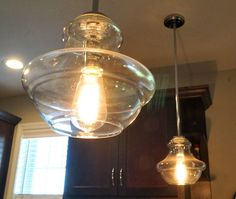 Glass light fixtures with exposed bulb in kitchen