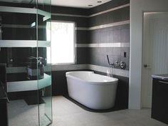 salle de bain noire et blanche avec baignoire ilot et cabine de douche