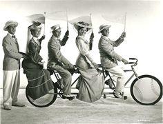 Betty Garrett, Frank Sinatra, Esther Williams and Gene Kelly ride a bike. Jules Munshin stands. 1949