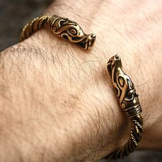 This is a solid bronze wolf heads and brass twisted wire handmade torc bracelet.  The bracelet is a replica of a similar torc bracelet found in the