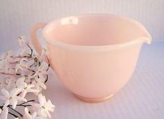 """A beautiful transluscent """"rose pink"""" pastel cream pitcher or measuring cup from the 1950s."""