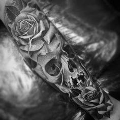 Linda tatuagem de crânio com manga comprida. Note que o crânio está envolto por rosas negras, o que forma um belo conjunto como tatuagem braçal. Uma das minhas tatuagens favorita.