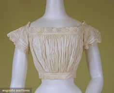 Whitework underbodice, 1860-1890; White cotton with whitework and eyelet trimmed short sleeves and wide squared neckline, inset waistband, machine and hand stitched