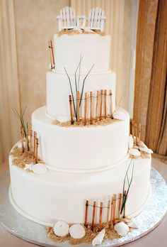 Beach wedding cake idea: White wedding cake with fences and sand