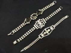 LOVELY GROUPING OF VINTAGE SILVER TONE RHINESTONE BRACELETS INCLUDING ONE WITH LARGE SMOKE STONES. ALL BUT ONE STONE ARE INTACT, PRONG SET AND BRILLIANT.