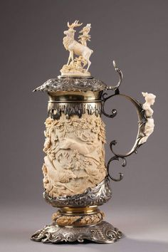A SILVER MOUNTED RELIEF CARVED IVORY TANKARD. 19 TH GERMAN WORK.