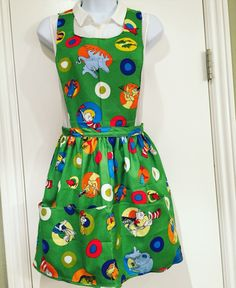 Vintage/Retro style apron!  Vibrant green Dr. Seuss apron with popular book characters!  Horton Hears a Who!, Green Eggs and Ham, Lorax!  Slightly ruffled waist, four varying sized pockets aligned at bottom of apron, ties at waist.  The upper portion of the apron loops over the neck - there are no fasteners, ties or buttons around the neck. Great for teacher appreciation, librarians, moms, volunteers!