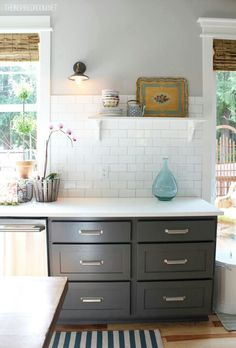 Updated kitchen with charcoal gray cabinets & soft gray walls, industrial light, natural shades & striped rug