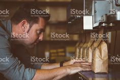 Worker looking at line of packed coffee beans royalty-free stock photo
