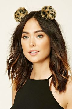 A headband featuring pom-pom embellishments with spotted faux fur.