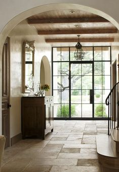 Entryway with paneled glass and steel door, bleached wood ceiling, limestone floor, plaster walls, and arched doorways.