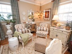 Two brown and white damask-patterned chairs are positioned in front a wicker ottoman creating an intimate sitting area. A low-hanging chandelier and an ornate white mirror draw the eye toward the back of the room with a few mirrored accent pieces. A distressed cabinet and blue plaid curtains give the room a more comfortable feel.