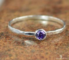 These dainty rings make a stunning fashion statement! This thin silver band is set with a dainty 3mm Amethyst Purple conflict free cubic zircon - February's birthstone! These rings are beautifully wor