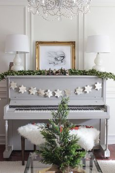 Gray piano, star garland, and framed Nativity pencil drawing on top