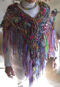 This is a fringed hand knit wrap with some needle felting.