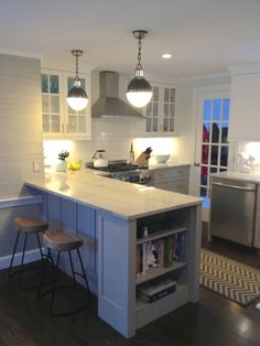 Beautiful kitchen with white upper cabinets in Classic White and gray lower cabinets painted Benjamin Moore Cape May Cobblestone paired with Bianco Macaubas Quartzite countertops and subway tile backsplash with Mist Grout. Visual comfort Lighting Thomas O'Brien Hicks