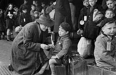 Young Evacuees 1942. A helper at Paddington Station in London fixing a label onto a child being evacuated from London during the war.