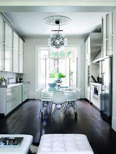 KJØKKEN med mørkt gulv, stort vindu i enden og høye vegger fylt med skap og skuffer.
