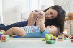 Mixed race mother playing with baby on floor