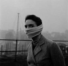 A lady with strings of pearls around her neck and a chiffon scarf around her nose and mouth during the Great Smog (London 1952).