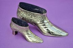 Delightful pair of silver-tone metal shows in the Victorian style with pincushion tops. Make a great gift for the collector or sewing enthusiast. Lovely décor for your craft or fabric shop.  The price shown is for the pair.  The shoes are very shiny with patterning as shown. They have a very expensive look and feel as they are quite heavy. The metal has some yellow wear marks on the front of the small shoe (image 4) although this does not detract from these superb vintage items. The…