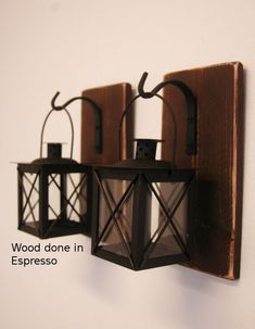 Overall Size: Wood base is 9.5 x 5 inches. Lantern in 4x4 inches square and 7 inches tall with the handle extended.  Gorgeous, unique and one-of-a-kind! Two black metal and glass lanterns each hanging from a wrought iron hook that is mounted to a recycled wood board.  The boards can be ordered in any color you wish. After they are painted they are given a distressed finish. *******See photo #5 for all available colors (using our painted milk bottle collection for available colors)  Photo #1…