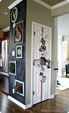 DIY Christmas card holder and chalkboard wall with empty frames to display decorations.